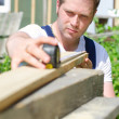 Handsome handyman measuring wooden plank outdoors — Stock Photo