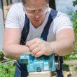 Handyman using electric planer outdoors — Stock Photo