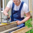 Handyman using polish machine outdoors — Stock Photo #28945477