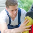 Young worker washing car with yellow sponge — Stock Photo