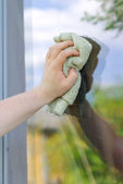 Male hand with rag washing window outdoors — Stock Photo