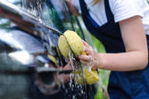 Female hand with yellow sponge washing car — Stock Photo