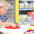 Cute little girl playing with blocks in supermarket — Stock Photo