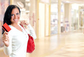 Young pretty woman in shopping center with credit card — Stock Photo