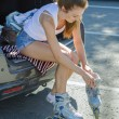 Girl sitting on the car and putting on inline skates. — Stock Photo