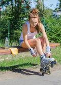 Красивая девушка сидит на скамейке и положить на роликовых коньков. — Стоковое фото