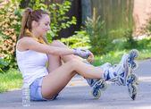 Jovem skatista feminina na estrada e amarra seus rolos — Fotografia Stock