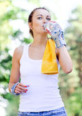 Female skater drinking water after training — Stock Photo