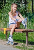Pretty girl sitting on the bench and putting on inline skates. — Stock Photo