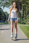 Woman with bottle of water ride rollerblades in the park. — Stock Photo