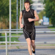 Young handsome sportsman running on the street — Stock Photo #30670629