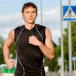 Young handsome sportsman running on the street — Stock Photo