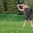 Young sportsman stretching before workout in park — Stock Photo #30670709