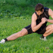 Young sportsman warming up before workout in park — Stock Photo
