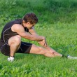 Young sportsman warming up before workout in park — Stock Photo #30670747