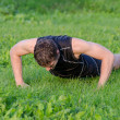 Handsome man doing push-ups at the park — Stock Photo