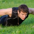Handsome man doing push-ups at the park — Stock Photo #30670785
