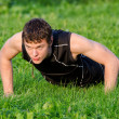 Handsome man doing push-ups at the park — Stock Photo #30670793