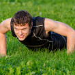 Handsome smiling man doing push-ups at the park — Stock Photo