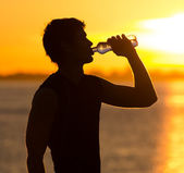 Man drinking bottle of water on the beach at sunrise — Stock Photo