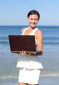 Attractive woman with notebook on the beach — Stock Photo