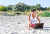 Attractive woman with laptop working on the beach. Place for text — Stock Photo