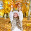 Little girl playing with fallen autumn leaves. — Stock Photo