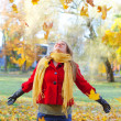 Happy woman throwing autumn leaves in the park. — Stock Photo