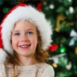 Happy little girl in santa's hat over christmas tree — Stock Photo