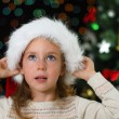 Little girl in santa's hat over christmas tree — Stockfoto #34087749