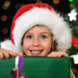 Little smiling girl with christmas gift. — Stock Photo