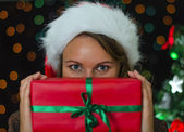 Attractive woman hiding behind a christmas gift. — Stock Photo