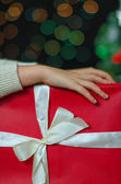Child hands holding christmas gift — Stock Photo