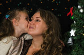 Little girl kissing her mother in christmas time — Stock Photo