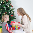 Mother giving her daughter christmas gift. — Stock Photo #35433725