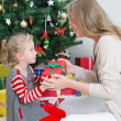 Mother giving her daughter christmas gift. — Stock Photo