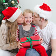 Parents kissing daughter in front of christmas tree. — Stock fotografie