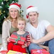 Happy family portrait in front of christmas tree. — Stockfoto
