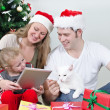Family with tablet pc in front of christmas tree. — Stock Photo