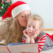 Little girl and her mom reading book at Christmas — Foto Stock