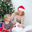 Woman and little girl playing with cat at Christmas — Stock Photo