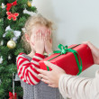 Woman surprising little girl with christmas gift — Stok fotoğraf