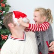 Father and daughter having fun at the christmas.  Girl trying to put on Santa's hat on father. — Stock Photo