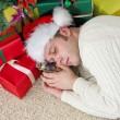 Drunk man with bottle sleeps under christmas tree — Stock Photo #35434075