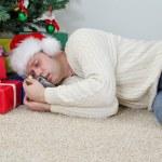 Drunk man with bottle sleeps under christmas tree — Stock Photo #35434087