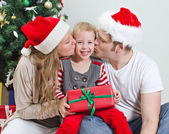 Parents kissing daughter in front of christmas tree. — Stock Photo