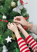Child hands and woman hands decorating the Christmas tree — Stok fotoğraf