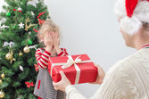 Father surprising little girl with christmas gift — Stock Photo