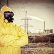 Man in chemical protective suit over factory — Stock Photo #35750645