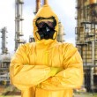 Man in chemical protective suit over factory — Stock Photo